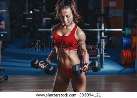 sexy young athletics girl doing biceps dumbbells curl exercises. Fitness muscled woman in red sport clothing workout with dumbbells in gym - stock photo