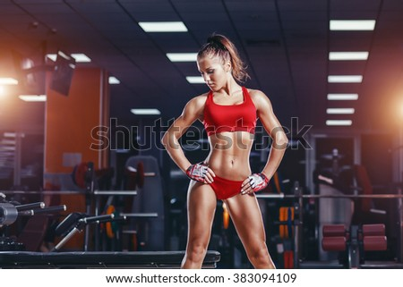 sexy young athletics girl resting after exercises. Fitness muscled woman in red sport clothing posing sitting on bench in gym - stock photo