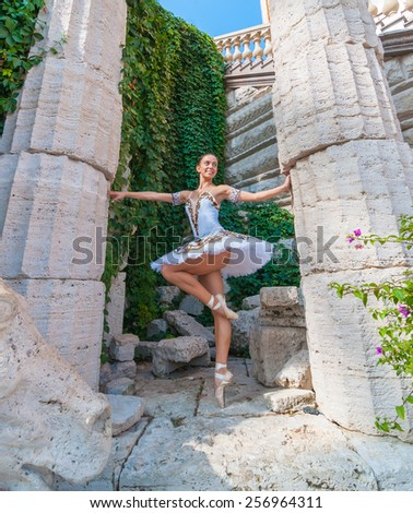 Sexy young ballerina dancing, posing and standing on tiptoes. Outdoors, spring