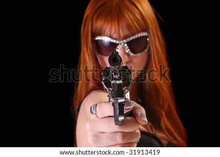 Sexy young beautiful redhead woman with revolver on black background - stock photo