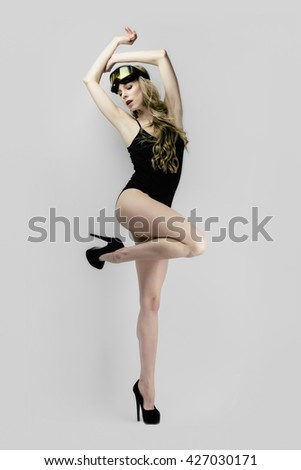 Sexy young beautiful sport woman posing in black modern bikini underwear vest lingerie with ski mask and high heels. High fashion studio photo of slim girl on grey background. - stock photo
