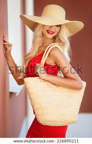 Sexy young beauty woman in red dress. beautiful fashionable blonde woman in red dress in hat with bag - stock photo