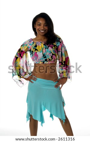 Sexy young Black woman in a blue skirt and a retro 60's pattern cropped blouse with a big smile and right hand to hip - stock photo