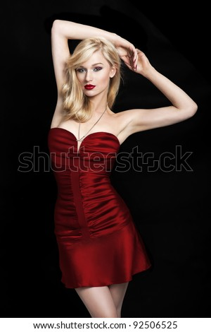 Sexy young blond woman in a red dress on a black background with her hands above the head - stock photo