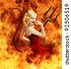 Sexy young blond woman in red dress as devil in fire with horns, tail and trident - stock photo