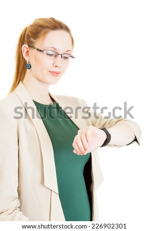 sexy young blonde girl wearing a green dress, jacket and glasses looks at watch - stock photo