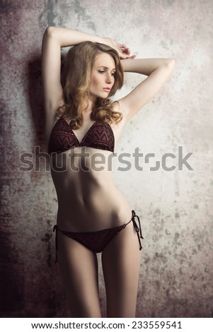 sexy young blonde girl with perfect body posing in glamour shoot with stylish bikini and long blonde hair  - stock photo