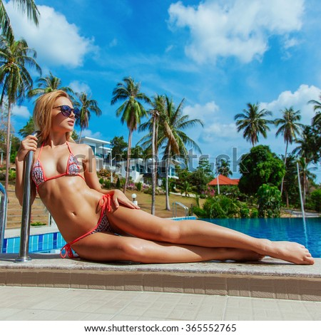 Sexy young blonde long legs woman lying on the pool get tanned and feeling happy on tropic island vacation  - stock photo