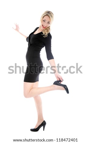 Sexy young blonde woman in black dress kicking back leg and touching her high heel isolated on white background - stock photo