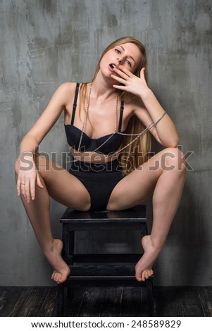 Sexy young blonde woman in black luxury lingerie posing against grungy gray wall. Passion and desire pose. Attractive woman with long precious chain in her hands - stock photo