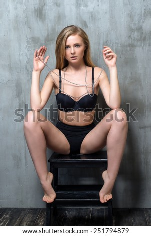 Sexy young blonde woman in black luxury lingerie posing against grungy gray wall. Passion and desire pose. Attractive woman with long precious chain in her hands. - stock photo