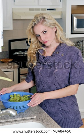 Sexy young blonde woman in kitchen washing grapes
