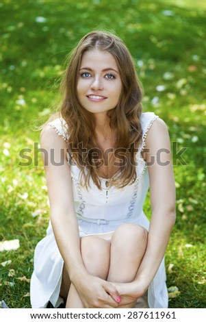 Sexy young blonde woman in white dress sitting on green grass in summer park - stock photo