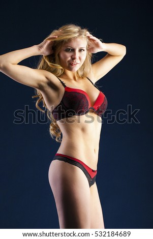 Sexy young blonde woman posing in red bikini over dark wall background