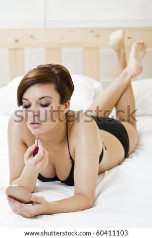 sexy young brunette girl on the bed applying herself a lipstick - stock photo
