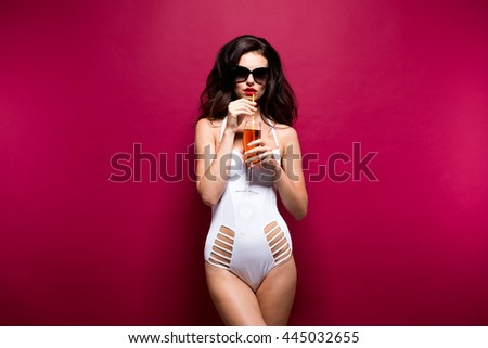 Sexy young brunette in sunglasses and white beachwear posing with red drink against of purple background.Isolated - stock photo