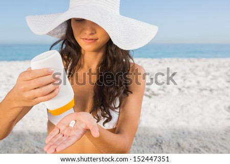 Sexy young brunette on the beach taking care of her body putting on sun cream - stock photo