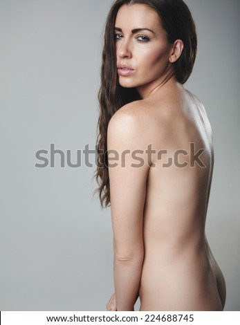 Sexy young brunette posing naked. Nude female model on grey background.