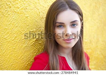 Sexy young brunette woman, against the background of the yellow wall - stock photo