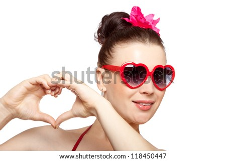 Sexy young brunette woman in heart-shaped glasses with purple flower in her hair showing heart shape with fingers against white background