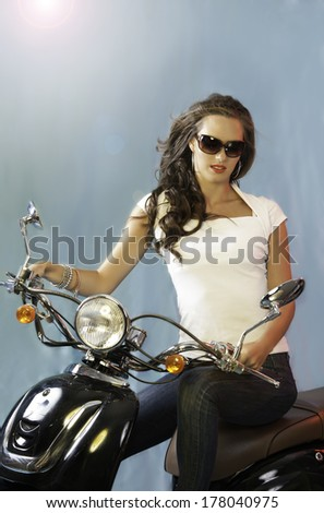 Sexy young brunette woman on scoot motorcycle wearing sun glasses, a white T shirt, jeans and messy hairstyle, posing against a turquoise background with lens flare from light behind her.  - stock photo