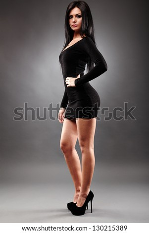 Sexy young brunette woman, wearing a mini black dress, in glamour full length, on gray background - stock photo