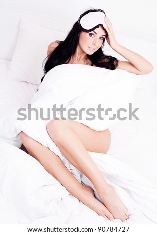 sexy young brunette woman wearing a sleep mask in bed at home - stock photo