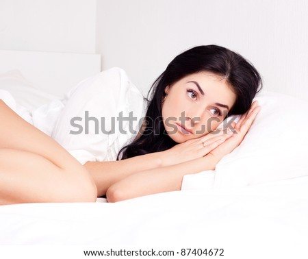 sexy young brunette woman wearing a white shirt on the bed at home - stock photo