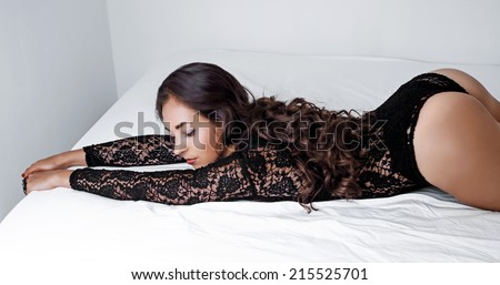 sexy young brunette woman with long curly hair in bed at home - stock photo