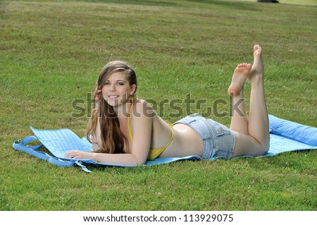 Sexy young Caucasian woman in yellow bikini top and jean shorts laying outside on blue mat - sunbathing and smiling at viewer