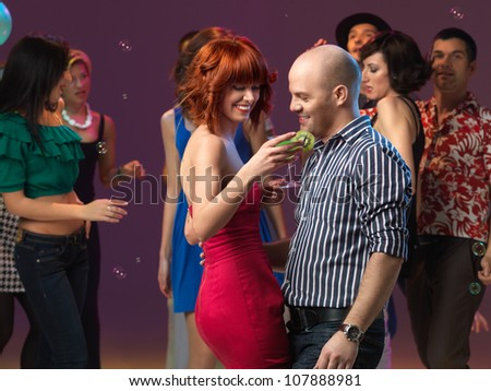 sexy, young couple having drinks on the dancefloor, in a night club