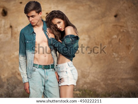 Sexy young couple in love wearing stylish trendy jeans posing outside. Casual free style. - stock photo