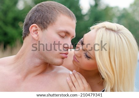 Sexy young couple kissing outdoors. - stock photo