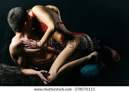 Sexy young couple of undressed sensual woman with straight body in red lace erotic lingerie sitting above muscular man kissing posing indoor on dark background, horizontal picture - stock photo