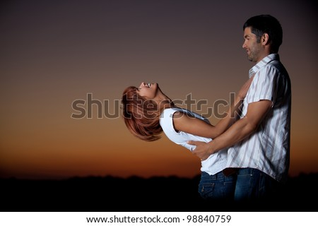 sexy, young couple playing holding each other on the beach, after sunset, smilling - stock photo