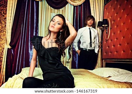 Sexy young couple playing in love games in a luxurious bedroom. - stock photo