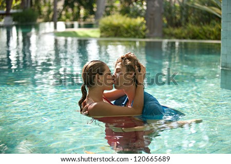 Sexy young couple submerged in a swimming pool while dressed, hugging and kissing while on a tropical destination vacation.