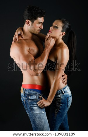 Sexy young couple with blue jeans standing together, studio shot - stock photo