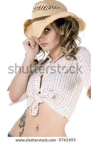 Sexy young cowgirl in a checkered blouse and straw cowboy hat - stock photo
