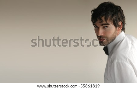 Sexy young elegant man turning toward camera against off white background and lots of copy space - stock photo