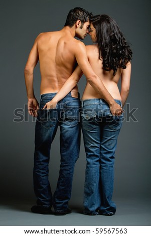 Sexy young ethnic couple in blue jeans - stock photo