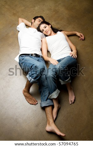 Sexy young ethnic couple in casual outfits relaxing - stock photo