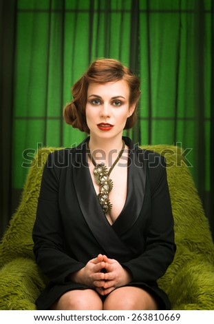 sexy young fashion model wearing black dress with cleavage, sitting on armchair - stock photo