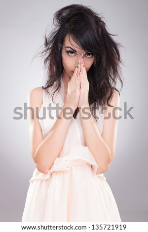 sexy young fashion woman holding her hands together in front of her face while looking at the camera. on gray background - stock photo