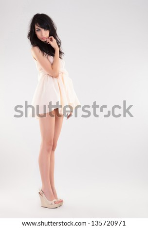 sexy young fashion woman looks at the camera with a sensual look, touching her chin with her hand. on gray background - stock photo