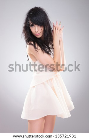 sexy young fashion woman standing with her hands together and with her hair roughed up. on gray background - stock photo