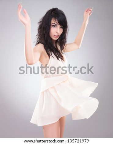 sexy young fashion woman standing with her hands up and looking at the camera while her dress is blown upwards. on gray background - stock photo