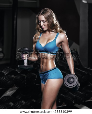sexy young girl exercises with dumbbells. Fitness woman in blue sport wear with perfect fitness body workout in gym - stock photo