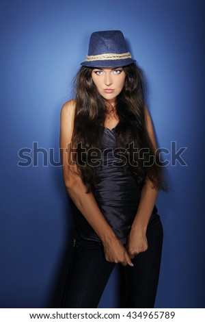 Sexy young girl, fashionista, blue hat, jeans, long brown hair, full lips, blue eyes, blue background, image 4.