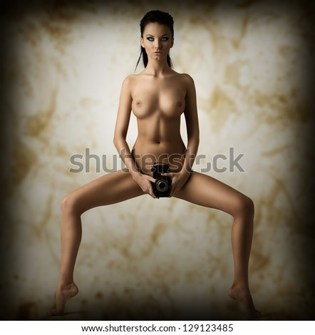 sexy young girl hot brunette takes camera on pubis and looking in camera - stock photo